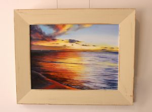 A framed original oil painting of a sunset on the Indian Ocean