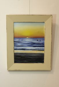 A framed original oil painting depicting a sunset at one of Perths popular beaches in summer