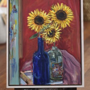 An original oil painting by Western Australian Artist Kiya Kalem depicting some bright yellow sunfloer blooms in a blue jar