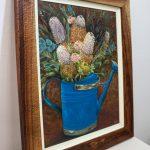 An original oil painting by Western Australian Artist Kiya Kalem depicting a bunch of Banksia blooms in a blue watering can