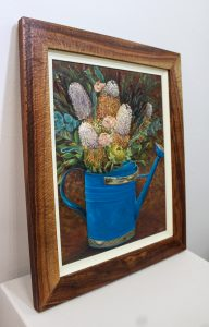 An original oil painting by Western Australian Artist Kiya Kalem depicting a bunch of Banksia blooms in a blue watering can